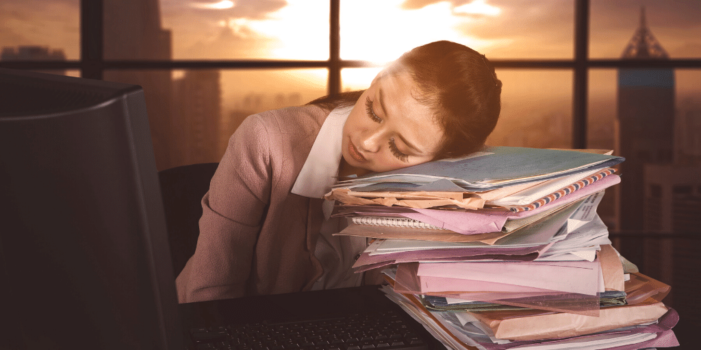 Overworked woman asleep at desk as sun comes up